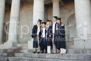 Five graduates posing while holding their diploma