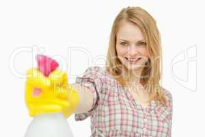 Woman holding a spray bottle while smiling