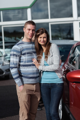 Couple holding tight while standing next to a car