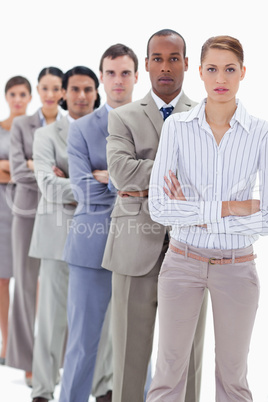 Serious colleagues dressed in suits crossing their arms in a sin