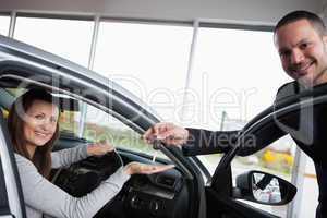 Woman sitting in her car while tending her hand