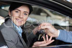 Smiling woman in a car receiving car keys