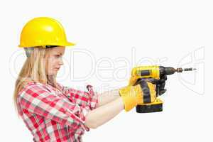 Serious woman using an electric screwdriver