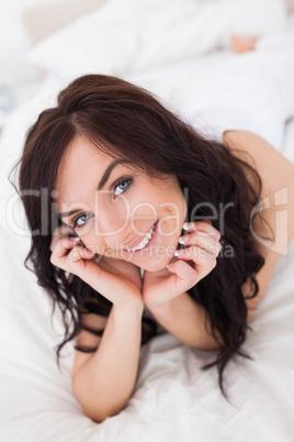 Joyful woman lying on her white quilt