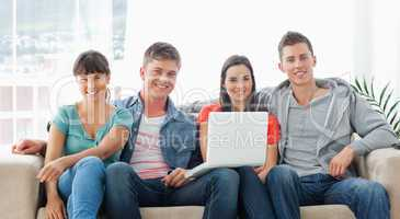 A group of friends sit on the couch with a laptop as they look a