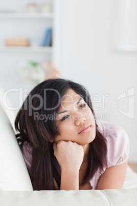 Thinking woman lying on a couch while holding her head with her