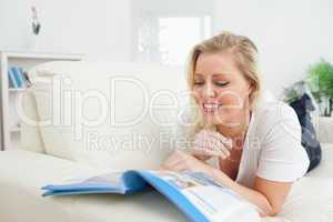 Casual woman lying and reading a booklet