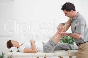 Physiotherapist massaging a leg while placing it on his shoulder