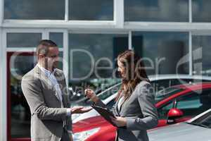 Businesswoman giving car keys to a client