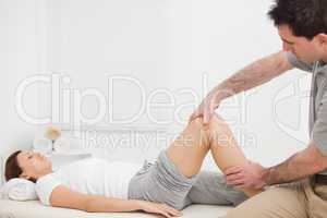 Brunette woman lying while a physiotherapist manipulates her leg