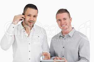 Smiling men holding a phone and a tablet computer