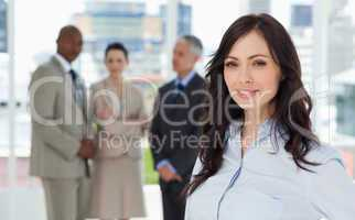 Businesswoman smiling and standing in a bright room with her tea