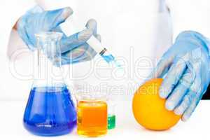 Chemist injecting product in an orange