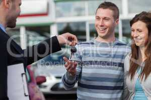 Couple receiving car keys by a dealer