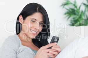 Woman holding a phone with two hands while sitting on a couch