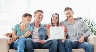 A laughing group sit together on the couch with a laptop watchin