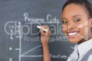 Focus on a teacher drawing a chart on a blackboard