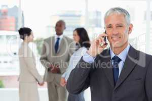 Smiling manager talking on the mobile phone while his team is be