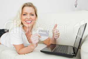 Woman with a thumb up and a credit card using a laptop