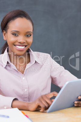 Teacher looking at camera while using a tablet computer