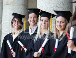 Portrait of smiling graduates posing in single line