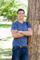 Portrait of a muscled student next to a tree
