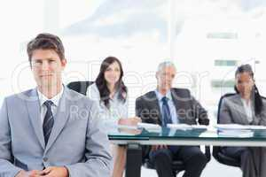 Earnest executive sitting in front of his team in a bright room