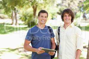 Close-up of two smiling male students with a touch pad