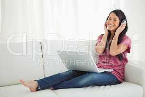 Smiling Latino student enjoying music on her sofa