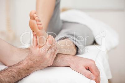 Woman having a foot massage while bending a leg