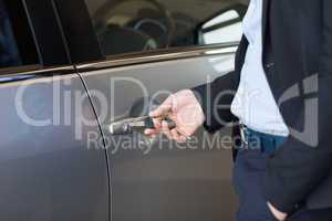 Man opening a car door with a key