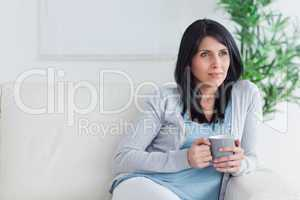 Thinking woman sits on a couch while holding a mug