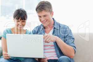 A pretty couple sitting while using a laptop together