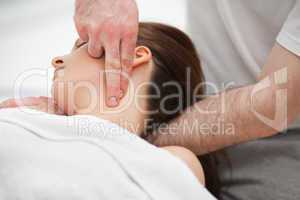 Doctor manipulating the neck of a woman while using his fingerti