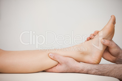 Chiropodist holding the calf of a patient