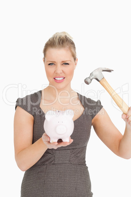 Concentrated woman want to break a piggy bank
