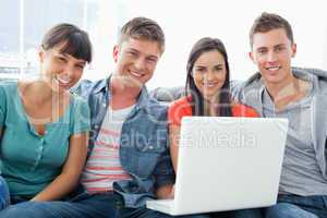 A smiling group of friends sitting together with a laptop as the