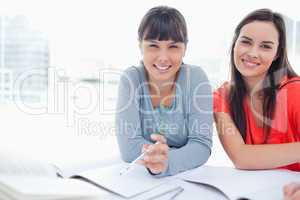 Two students sitting beside each other smiling as they work