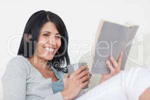 Woman smiling while holding a grey mug and a book