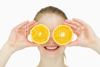 Close up of a smiling woman placing oranges on her eyes