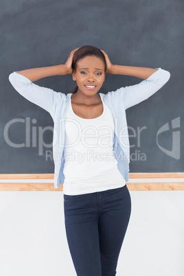 Black woman upset next to a blackboard
