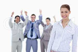 Close-up of a secretary smiling with enthusiastic business peopl
