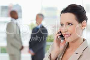 Young secretary talking on the phone while smiling and looking t