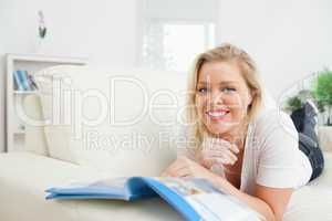 Woman smiling while reading a booklet