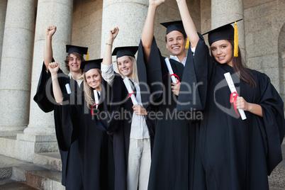Five happy graduates posing the arm raised