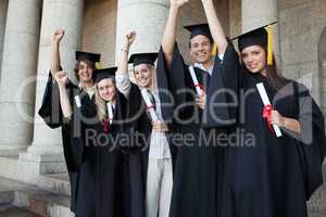Five happy graduates posing the arm raised