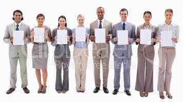 Business people smiling while holding support for letters