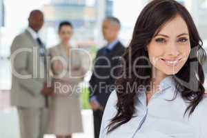 Young executive woman smiling and looking ahead with the team in