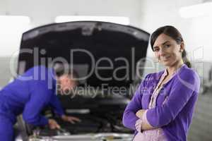 Smiling woman looking at camera next to a car