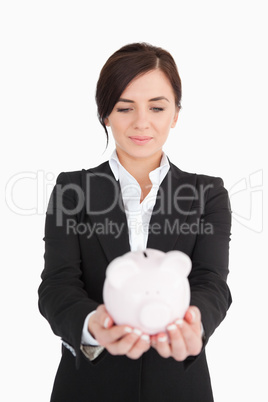 Businesswoman looking at a piggy-bank